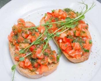 тарелка с двумя брускеттами с лососем, томатами и соусом песто
