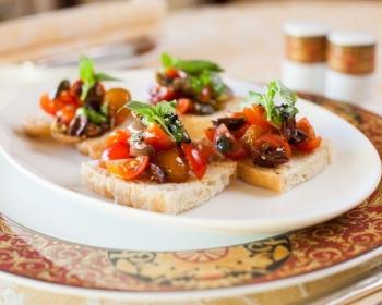 брускетта с кусочками помидоров, оливками и зеленью на белой плоской тарелке на столе