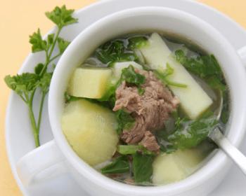 бухлер с бараниной, картофелем и большим количеством зелени в белой глубокой чаше на тарелке