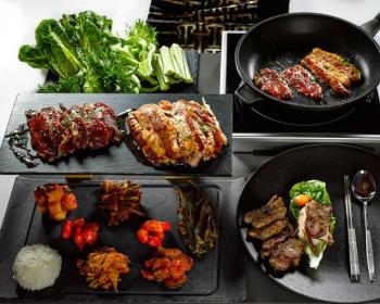 бульгоги на сковороде и на тарелке, ряжом поднос с жареным мясом, специями, рисом и листьями салата, а также столовые приборы