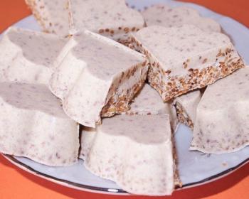 кусочки бурфи с кунжутом на белой тарелке на столе