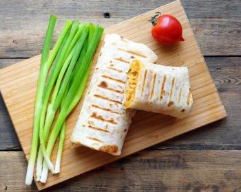 два буррито с начинкой внутри, помидор и зеленый лук на деревянной разделочной доске на столе