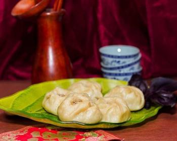 отваренные буузы на зеленой тарелке в форме листочка на столе, на фоне пиалы для чая голубого цвета и деревянный кувшин