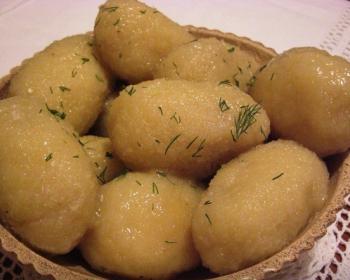 вареные картофельные цеппелины с мясом, присыпанные зеленью, в тарелке на столе, застеленном скатертью