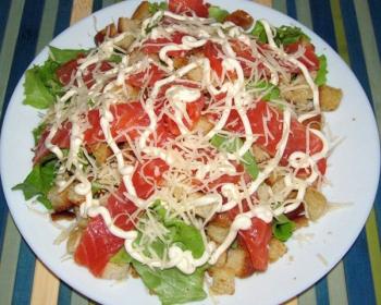 салат цезарь из кусочков семги, листьев салата, сухариков и тертого твердого сыра, заправленный майонезом, на белой плоской тарелке на столе