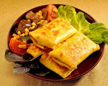 две запеченные чимичанги с салатным листом, нарезанными помидорами и консервированной кукурузой на коричневой тарелке на столе