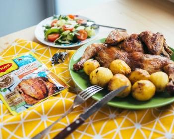 тарелка с запеченной картошкой и цыпленком на столе, застеленном желтой скатертью, рядом тарелка с овощным салатом и пачка с приправой