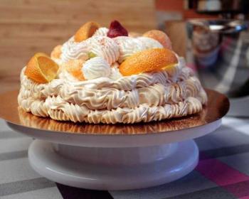 десерт Павлова из безе с фруктами на подставке для торта
