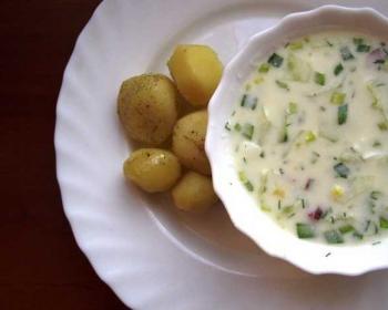 на большой белой тарелке стоит белая пиала с диетической окрошкой для похудения, рядом лежит вареный картофель
