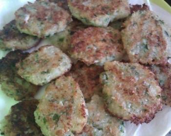 жареные капустные котлеты с зеленью, сложенные друг на друга, на белой тарелке, застеленной салфеткой