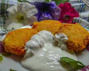 три жареные морковные котлеты со сметаной на тарелке на столе, застеленном скатертью, рядом цветочки