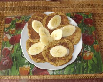 диетические панкейки с нарезанными бананами в тарелке на столе