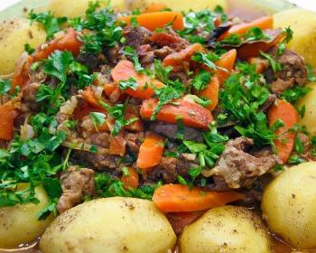димлама из вареного картофеля с помидорами и тушеных кусочков мяса, посыпанных рубленой зеленью, в тарелке