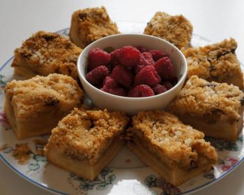 домашний пирог с яблоками, нарезанный на порционные кусочки, выложенный по кругу на большом блюде, внутри стоит маленькая пиала с малиной