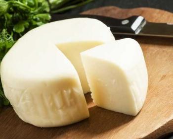 головка домашнего сыра с отрезанным треугольным кусочком лежит на деревянной разделочной доске, рядом лежит нож