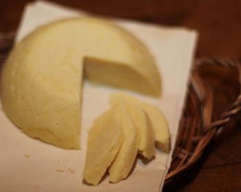 домашний твердый сыр с отрезанными кусочками на бумаге в корзине