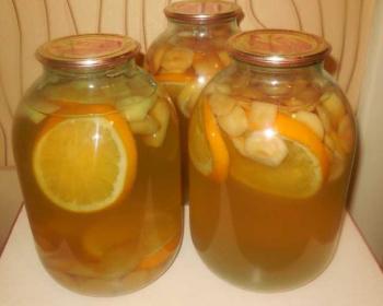три трехлитровых банки домашней фанты с апельсинами, лимонами и яблоками на кухонном столе