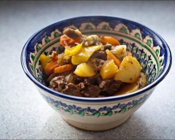 дымляма из кусочков картофеля, баранины, репчатого лука и сладкого перца в глубокой тарелке на столе