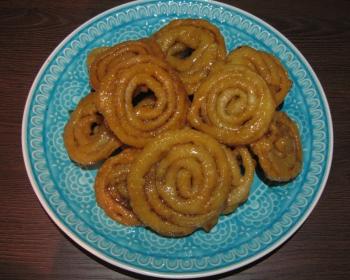 джалеби, политые сиропом и сложенные в голубую тарелку, на столе