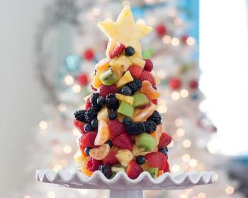 на белой подставке из фруктов стоит елочка из фруктов, украшают изделие ежевика, клубника, киви, мандарины, а сверху стоит звезда, вырезанная из ананаса