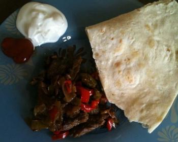 фахитос с говядиной со сметаной, томатным соусом и лепешкой на синей тарелке с узором