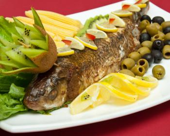 фаршированная рыба, запеченная в духовке целиком, Лявянги, лежит на большом блюде, голова украшена короной из киви, лимон, нарезанный спиралью, маслины и оливки, беби-кукуруза и листья салата украшают блюдо
