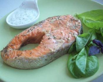 форель, запеченная в духовке в фольге, на тарелке в сочетании с соусом и листьями шпината