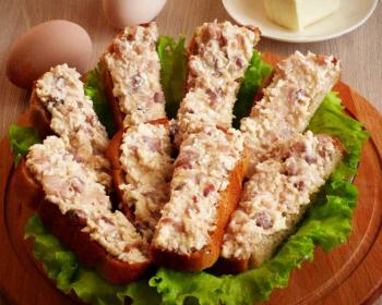 форшмак из сельди на хлебе с листьями салата на тарелке на деревянной подставке, яйца на столе