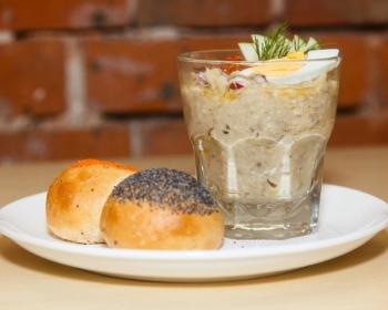 белая тарелка на столе, на ней лежат свежие булочки и стоит стакан с форшмаком по-еврейски, украшенным свежей зеленью и вареным яйцом