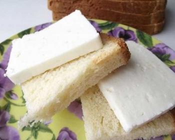 ломтики домашнего белого французского хлеба с кусочками сыра на тарелке на столе