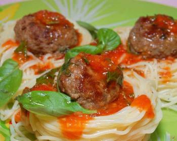 """три фрикадельки в томатном соусе, приготовленные на сковороде, в """"гнездах"""" из макарон со свежими листьями базилика"""