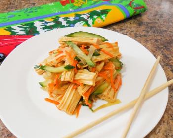 тарелка с фучжу, морковью и огурцами на столе, китайские палочки для еды, разноцветная салфетка на фоне