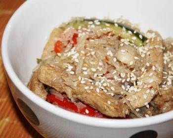 фунчоза с кусочками свинины, грибов, огурца и сладкого перца, присыпанная кунжутом, в белой тарелке на столе