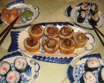 роллы с разной начинкой на тарелках в форме рыбок на столе с китайскими палочками