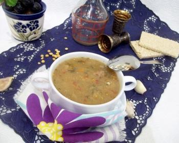 порция горохового супа с фрикадельками в супнице на столе, застеленном фиолетовой салфеткой, рядом зубчики чеснока, ложка, стакан и металлические рюмочки