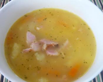 гороховый суп с кусочками курицы, картофеля и моркови в глубокой белой тарелке