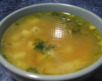 гороховый суп с зеленью в тарелке на столе