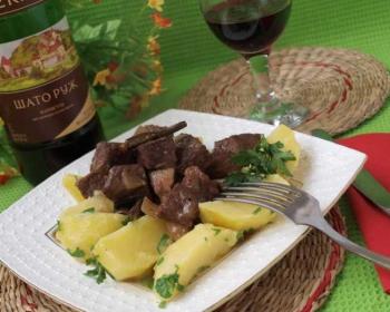 на белой квадратной тарелке лежит вареный картофель, сверху лежит говядина по-бургундски, нарезанная кусочками, рядом лежит столовый нож, на краю тарелки лежит вилка, рядом стоит бутылка вина