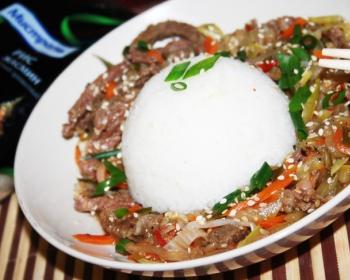 тушеные кусочки говядины, перемешанные с морковью и зеленью, с вареным рисом, присыпанным кунжутом, на белой тарелке