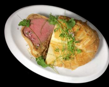 говядина Веллингтон, запеченная в тесте, лежит на белой овальной тарелке, сверху на блюде лежит свежая зелень