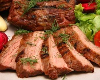 говядина, запеченная в рукаве и нарезанная на кусочки, лежит на большой тарелке, сверху мясо, присыпанное свежей зеленью укропа, рядом лежат помидоры, разрезанные пополам, головка чеснока и свежие листья салата