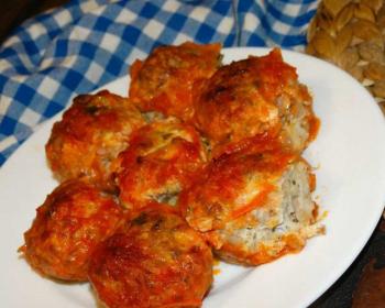 гречаники в томатном соусе в белой тарелке на столе, на фоне клетчатая бело-синяя салфетка