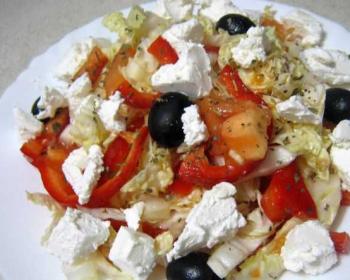 салат с помидорами, маслинами, сыром фета, пекинской капустой и красным перцем на тарелке