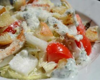 на белой тарелке лежит греческий с курицей, сухариками и помидорами