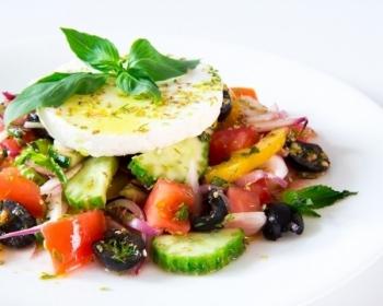 салат из сыра фета, огурцов, маслин, помидоров и лука, украшенный листиками мяты, на белой плоской тарелке