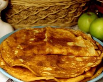 на голубой тарелке лежат блинчики стопкой, один блинчик свернутый треугольником, рядом лежат два яблока