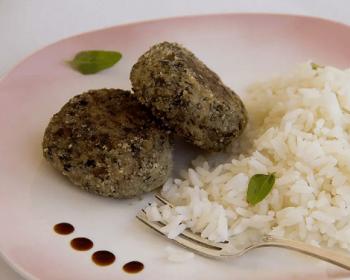две картофельно-грибные котлеты на тарелке с вареным рисом
