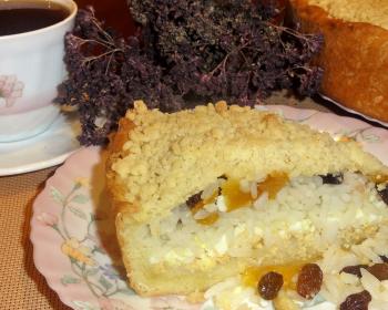 кусок сладкой губадии с рисом, творогом, изюмом и курагой на тарелке на столе, рядом чашка с чаем