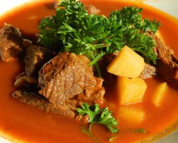 гуляш из свинины, приготовленный в мультиварке, с кусочками картофеля, в томатном соусе, украшено блюдо несколькими веточками петрушки