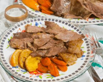 мясо гуся с апельсинами и морковью на тарелке